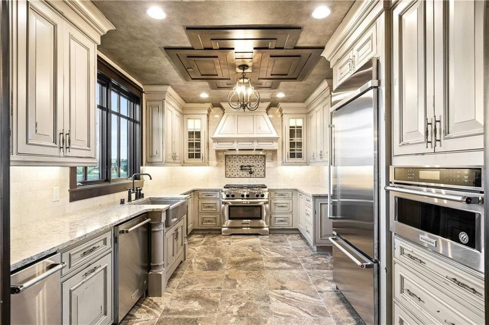 This other kitchen has a long and narrow design. It has beige tones to its cabinetry that lines the walls which complements the stainless steel appliances. Image courtesy of Toptenrealestatedeals.com.