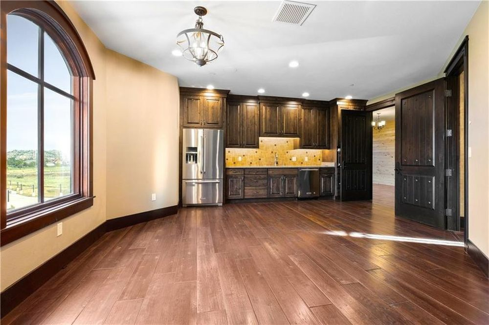 This other kitchen has a spacious dark hardwood flooring with enough space for an informal dining area. On the far side are dark wooden cabinetry that makes the stainless steel fridge stand out. Image courtesy of Toptenrealestatedeals.com.
