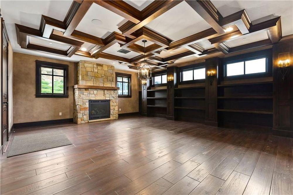 The library has a large stone fireplace on the far side and a row of built-in wooden bookshelves running the wall on the side. Image courtesy of Toptenrealestatedeals.com.