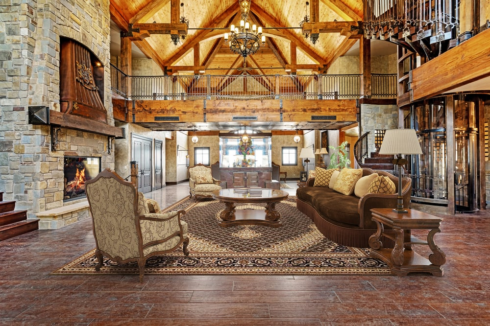This other view of the formal living room shows the large stone fireplace on the side. You can also see here the tall cathedral ceiling and an indoor balcony on the second level. Image courtesy of Toptenrealestatedeals.com.