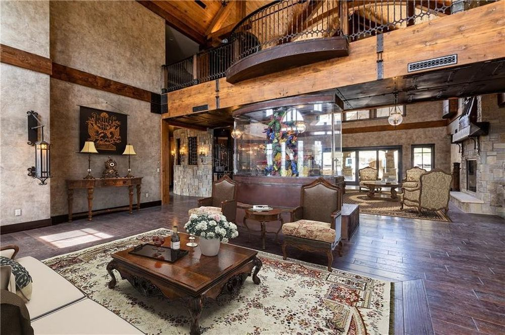 This is the other living room on the other side of the large open room. It has a couple of sofas flanking a large wooden coffee table on an area rug. Image courtesy of Toptenrealestatedeals.com.