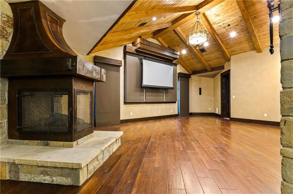 This is the media room with a built-in white screen that rolls down for the projector. On the side is a large fireplace to warm the room. Image courtesy of Toptenrealestatedeals.com.