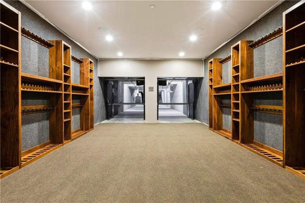 This is the shooting range of the house. It has wooden racks on both walls for gun storage and on the far side is the actual two-person shooting range. Image courtesy of Toptenrealestatedeals.com.