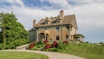 This is the exterior view of the mansion with stone granite walls adorned with dormer windows, tall chimneys and a colorful garden. Image courtesy of Toptenrealestatedeals.com.