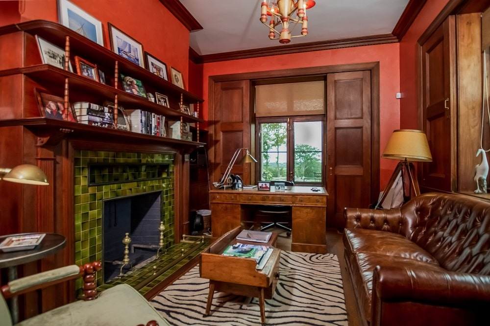 The home office has vibrant and earthy red walls that complement the dark brown tones. You can also see here the sofa and fireplace across from each other. Image courtesy of Toptenrealestatedeals.com.