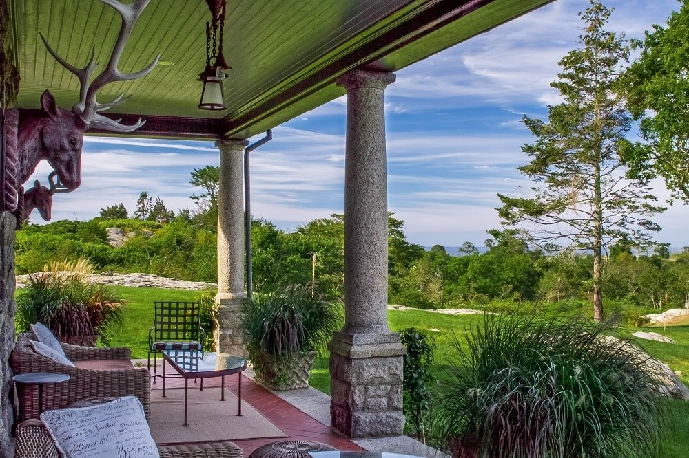 This is the covered patio with its outdoor iron chairs under a tall ceiling supported by concrete and stone pillars. Image courtesy of Toptenrealestatedeals.com.