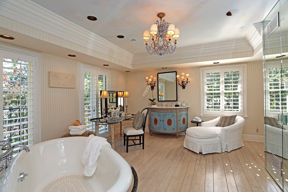 The primary bathroom has a freestanding bathtub that stands out against the beige tiles and walls. This pairs well with the lounge chair and the window shutters. Image courtesy of Toptenrealestatedeals.com.