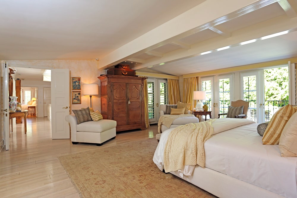 The spacious primary bedroom has an arched beige ceiling with an exposed beam in the middle above the bed. Across from this is a large wooden French cabinet by the cushioned chair. Image courtesy of Toptenrealestatedeals.com.