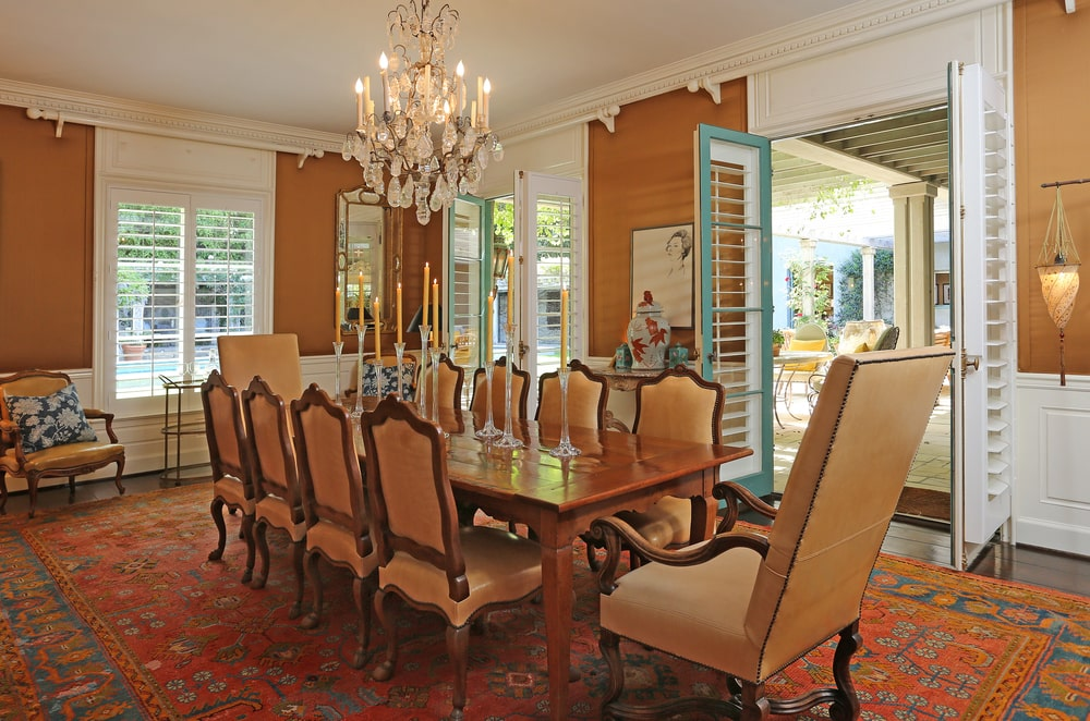 The formal dining room has a long wooden dining table topped with a chandelier that hangs from the beige ceiling. Image courtesy of Toptenrealestatedeals.com.