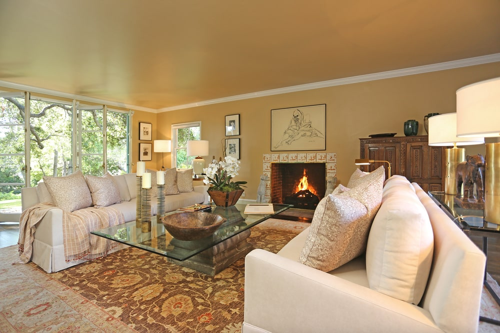 The family room has a couple of beige sofas flanking the glass-top coffee table across from the fireplace with a beige mantle that blends with the walls. Image courtesy of Toptenrealestatedeals.com.