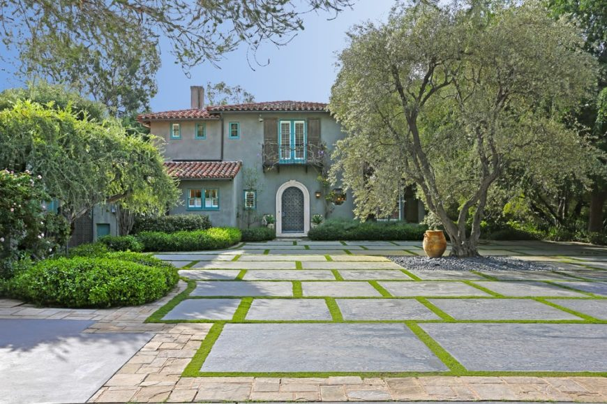 A look at the front of the house featuring a landscape of a concrete courtyard adorned with trees and well-manicured shrubs that complement the gray tone of the exteriors. Image courtesy of Toptenrealestatedeals.com.