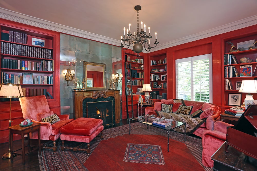The library has a vibrant red tone to its walls, built-in bookshelves and the area rug that pairs with the cushions of the sofa set. Image courtesy of Toptenrealestatedeals.com.