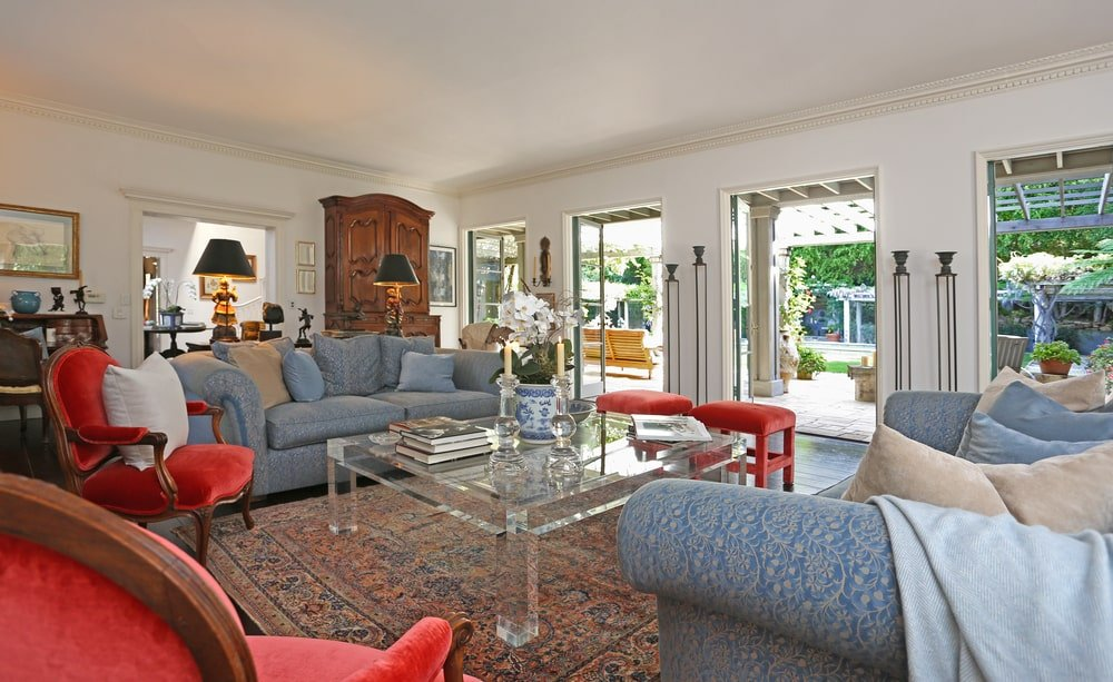 The living room has a gray sofa set that stands out against the red patterned area rug with a modern see-through coffee table in the middle. Image courtesy of Toptenrealestatedeals.com.