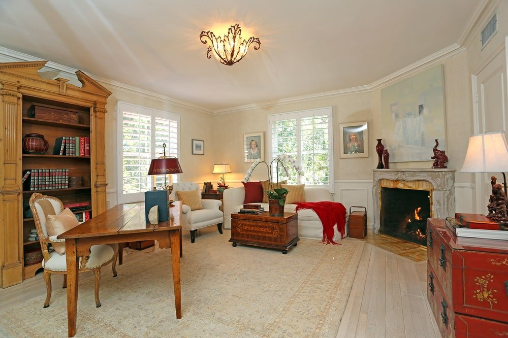 The home office has beige walls and ceiling that makes the wooden furniture stand out. These are then complemented by the fireplace across from the wooden desk. Image courtesy of Toptenrealestatedeals.com.