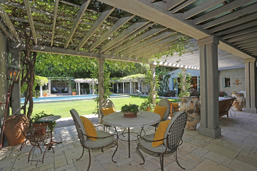 This is a covered patio just a few steps from the swimming pool. This is topped with trellises covered with creeping plants to provide shade. Image courtesy of Toptenrealestatedeals.com.