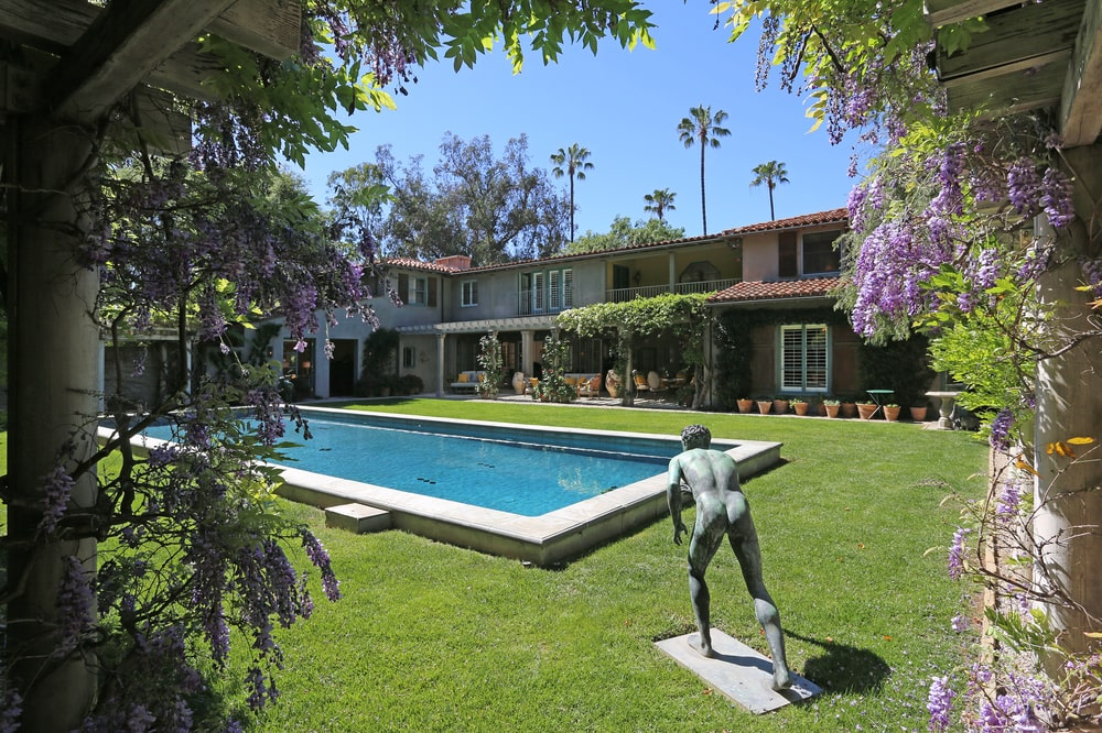 A close look at the swimming pool shows the grass lawn surrounding it adorned with a concrete statuette. Image courtesy of Toptenrealestatedeals.com.