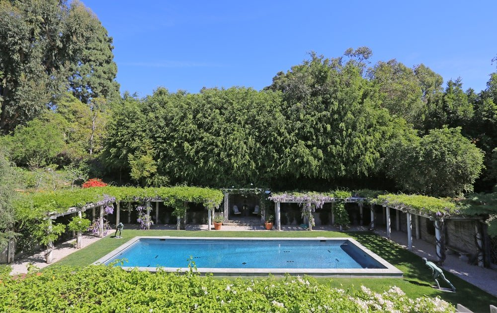 This is the backyard pool from the vantage of the second-floor balcony. You can see here that it is surrounded by covered walkways and areas under trellises filled with creeping plants. Next to it is a background of tall trees. Image courtesy of Toptenrealestatedeals.com.