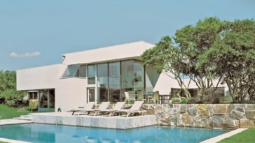 This is a look at the back of the house with crisp white exterior walls, glass walls and a large stone planter on the side with a tall tree by the swimming pool. Image courtesy of Toptenrealestatedeals.com.