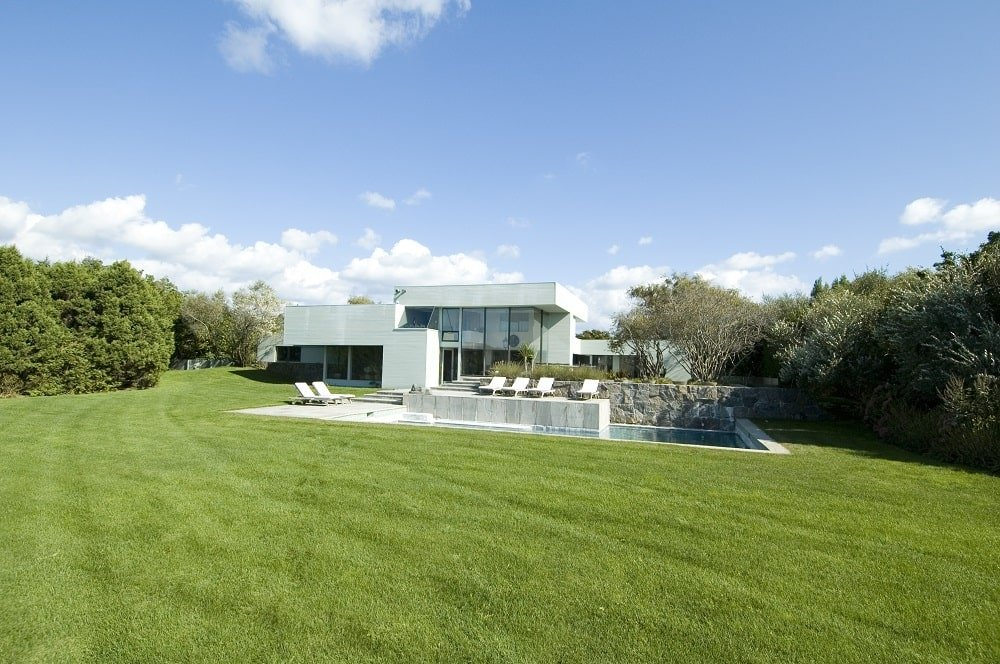 This is a close look at the landscaping surrounding the house that is filled with wide grass lawns and tall trees that complement the modern contemporary house with glass walls. Image courtesy of Toptenrealestatedeals.com.