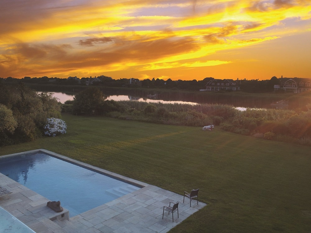 This is a look at the scenery of the backyard swimming pool that is surrounded by stone walkways before transitioning to a wide grass lawn that leads to the water edge a few yards away. Image courtesy of Toptenrealestatedeals.com.