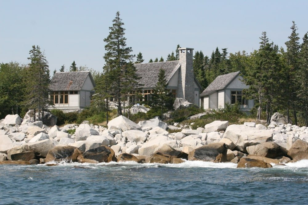 This is an aerial view of the three structures from the vantage of the ocean. Here you can see the gray tone of the exterior walls that stand out against the rocks and tall trees of the landscape. Image courtesy of Toptenrealestatedeals.com.