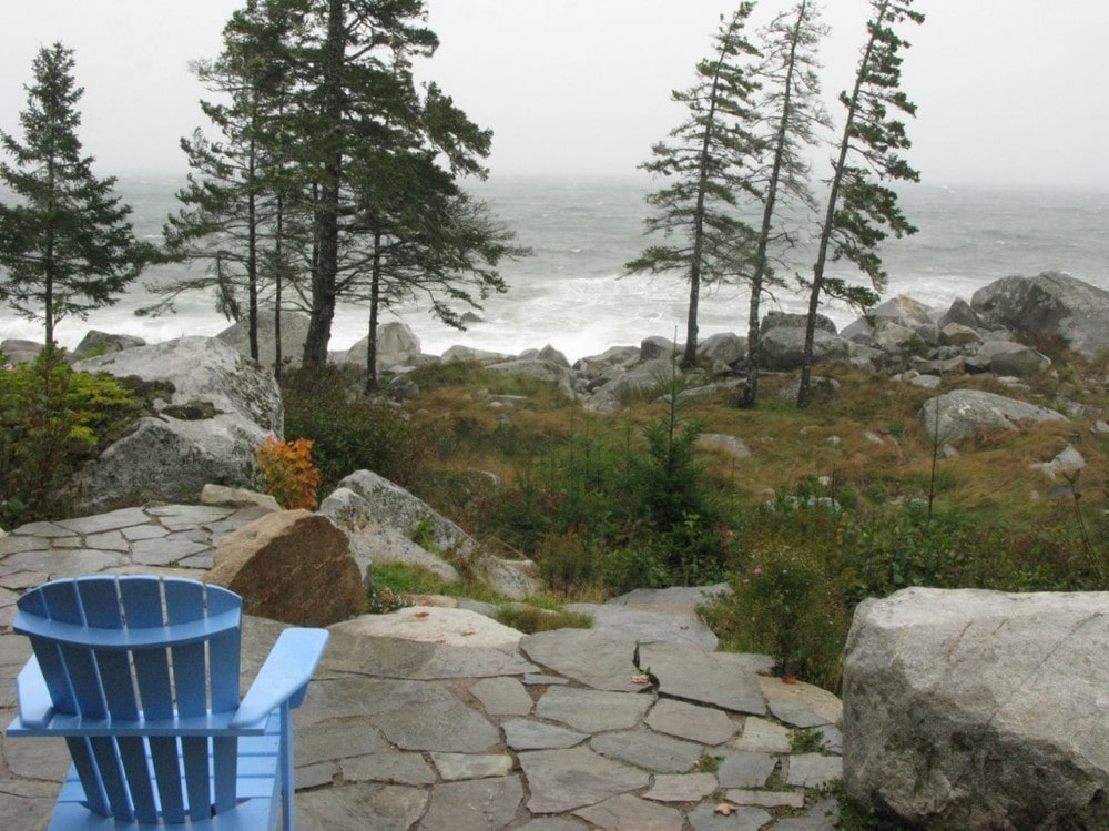 This is the outdoor patio with a mosaic stone flooring leading to stone steps to the ocean. This is fitted with a wooden armchair to better enjoy the view. Image courtesy of Toptenrealestatedeals.com.
