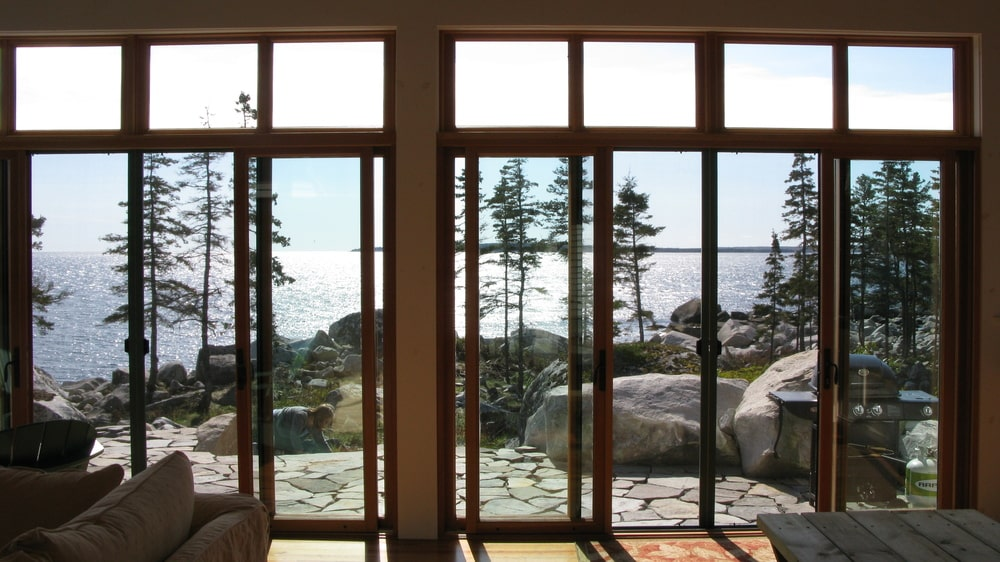 This is a look at the ocean view afforded by the large glass wall and doors of the main building. These are then complemented by the wooden frames. Image courtesy of Toptenrealestatedeals.com.