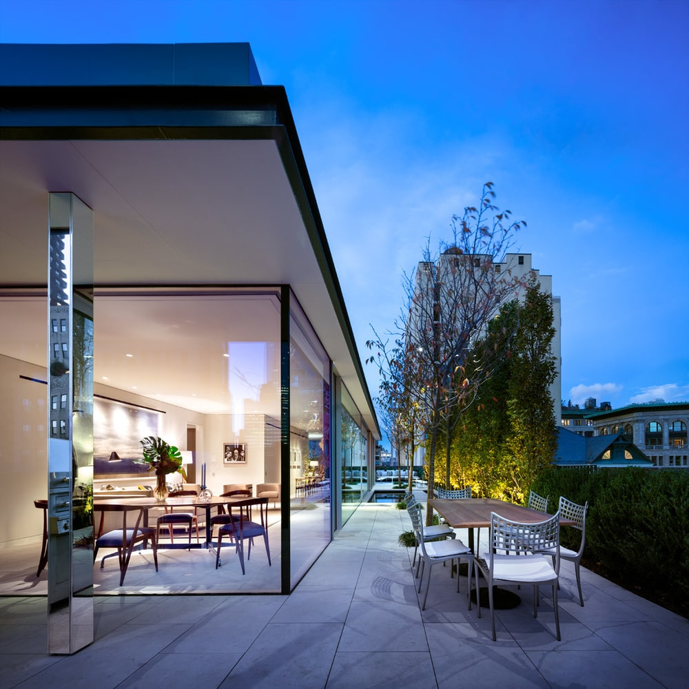 This is a look at the outdoor patio of the penthouse just outside the glass wall. This is fitted with an outdoor dining area adorned by the landscape of shrubs and tall trees. Image courtesy of Toptenrealestatedeals.com.