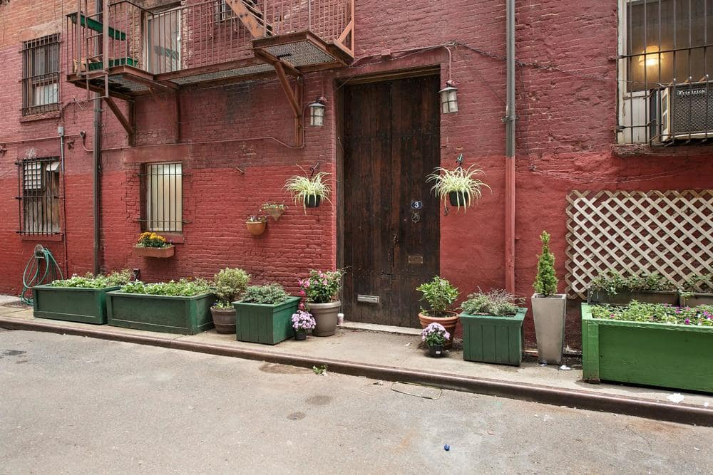 This is a look at the main entrance of the house. You can see here the red stone exterior walls and the original wooden stable doors flanked by sconces and potted plants. Image courtesy of Toptenrealestatedeals.com.