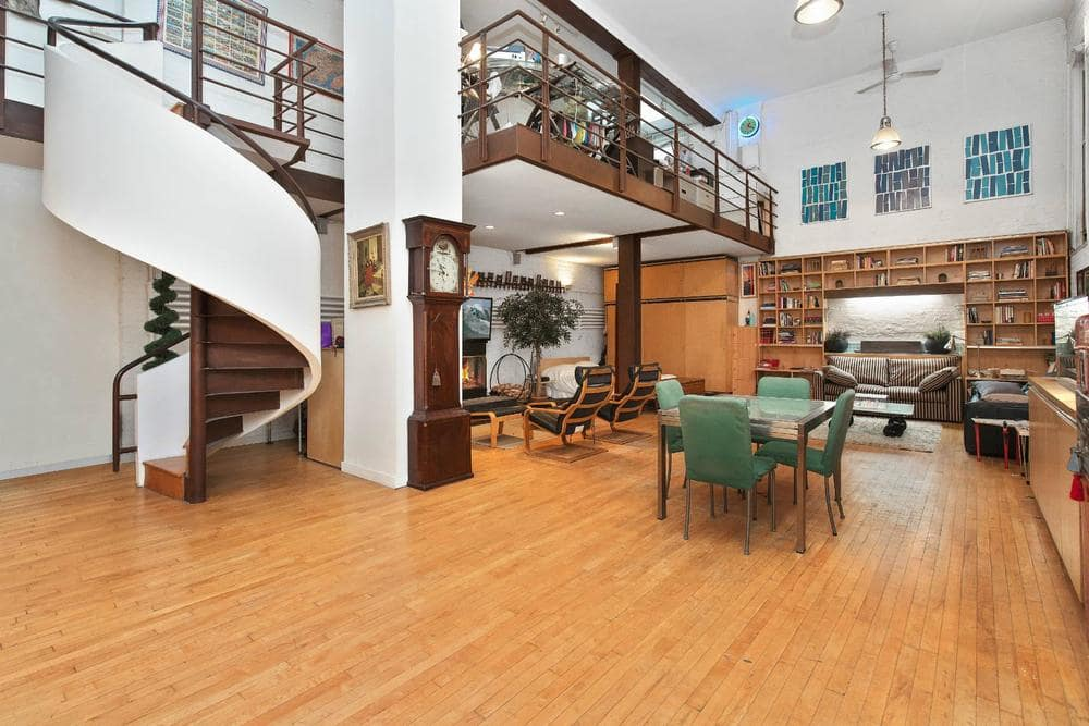 This is a view of the open-style interiors from the vantage of the foyer. The dining, living room area and the library at the far end are all on the same spacious hardwood flooring. Image courtesy of Toptenrealestatedeals.com.
