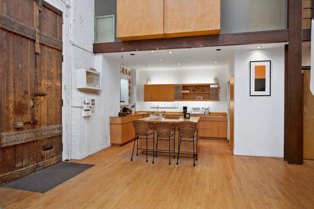Upon entry of the main door, you will see the eat-in kitchen on the left side with wooden cabinetry that matches well with the hardwood flooring. Image courtesy of Toptenrealestatedeals.com.