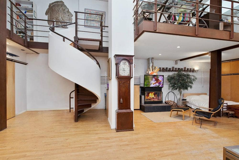 This view of the great room showcases the spiral staircase that leads to the second level loft with iron railings for the indoor balcony. Image courtesy of Toptenrealestatedeals.com.