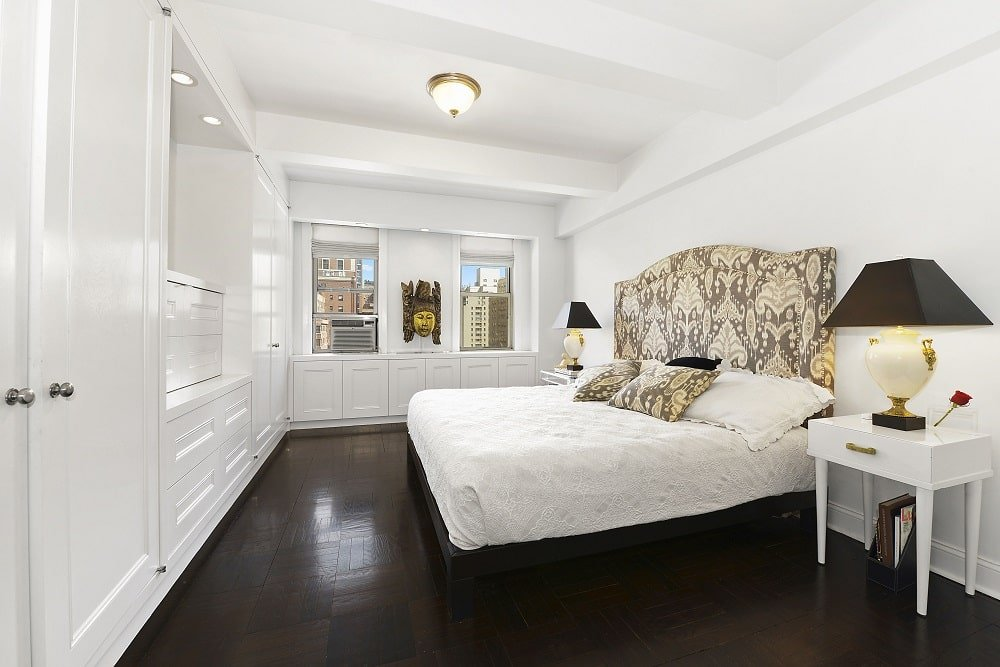 The bedroom has a dark hardwood flooring that contrasts the bright tones of the bed, walls and ceiling. Across from the bed is a built-in white cabinet dominating the whole wall. Image courtesy of Toptenrealestatedeals.com.