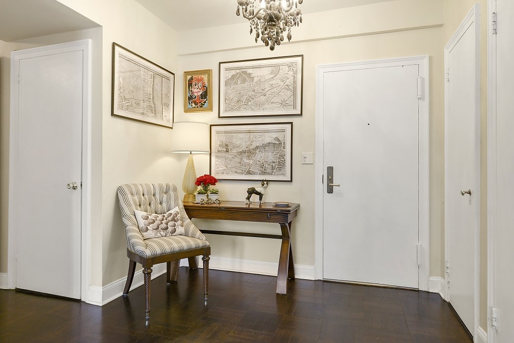 Upon entry of the apartment, you are welcomed by this small foyer with a wooden console table on the side with a cushioned chair for waiting guests. Image courtesy of Toptenrealestatedeals.com.
