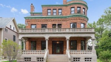 This is the front view of the brick mansion with a large entry porch, three levels and rows of glass windows that stand out against the red brick exteriors. Image courtesy of Toptenrealestatedeals.com.