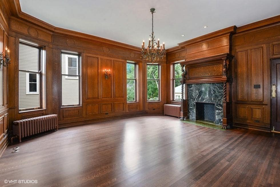 This is the wood-paneled library with a black stone fireplace and a small chandelier hanging from the white ceiling. Image courtesy of Toptenrealestatedeals.com.