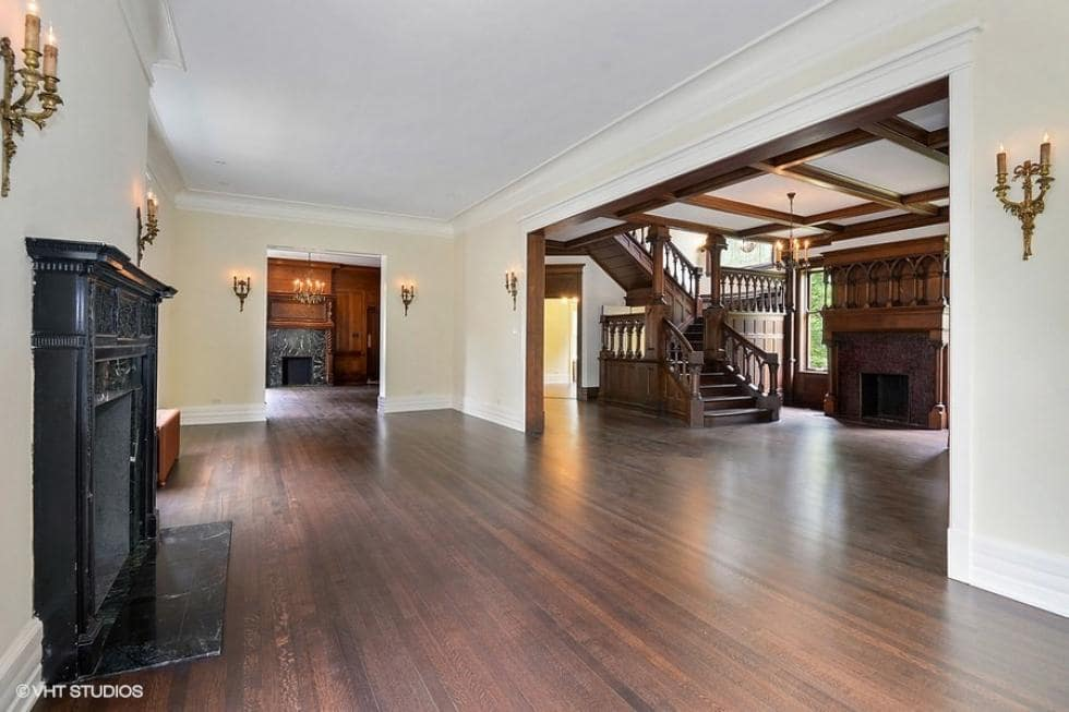 A few steps from the foyer is this living room area with a fireplace and dark hardwood flooring. Image courtesy of Toptenrealestatedeals.com.