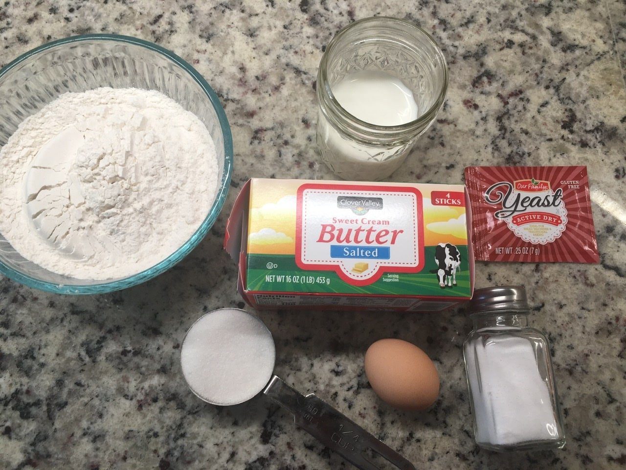 Dough ingredients including a baking powder, butter, milk, yeast, salt, and egg over a marble countertop.