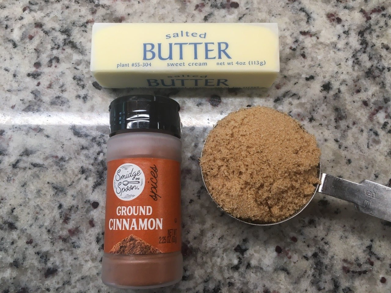 Filling ingredients including a butter, ground cinnamon, and a spoonful of brown sugar against a marble countertop.