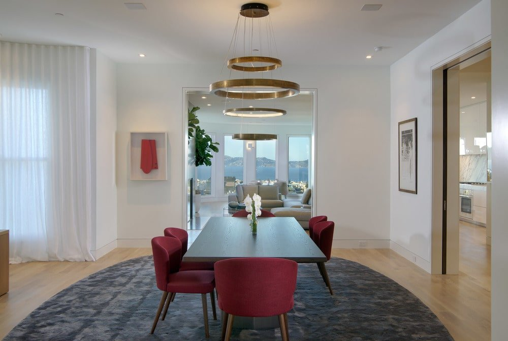 This is the dining room with a dark wooden dining table to match the dark area rug underneath. These are then contrasted by the red cushioned chairs and the beige walls. Image courtesy of Toptenrealestatedeals.com.