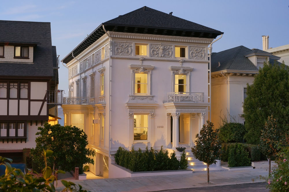 This is a look at the front of the mansion with bright exterior walls contrasted by the dark roof and complemented by the warm lights, windows and shrubs. Image courtesy of Toptenrealestatedeals.com.
