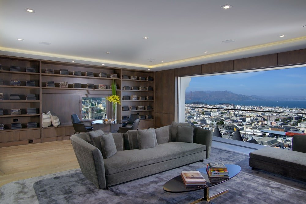 This is the living room that has a gray sofa on a gray area rug and a large dark wood structure at the far wall with built-in shelves. Image courtesy of Toptenrealestatedeals.com.