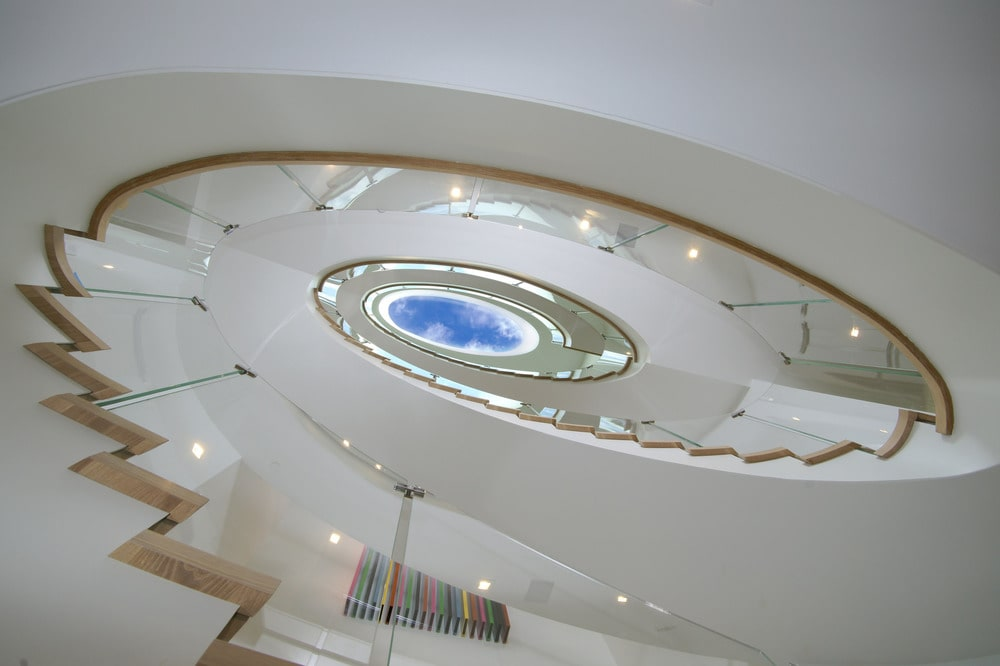 This is a look at the spiral staircase of the mansion with bright white tone and glass railings. Image courtesy of Toptenrealestatedeals.com.