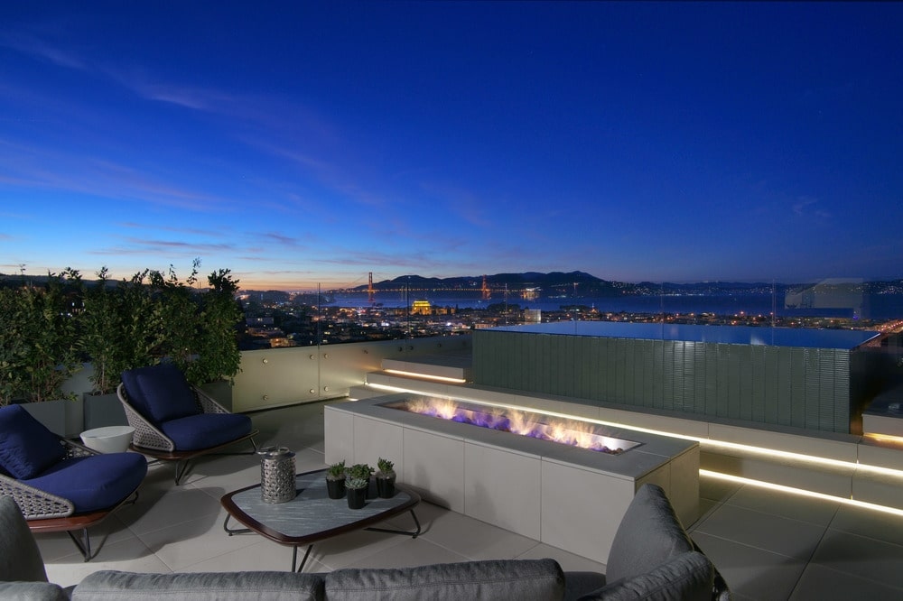 This is a look at the view of the city from the vantage of the balcony that is warmed by a modern fire pit paired with a sofa and a coffee table. Image courtesy of Toptenrealestatedeals.com.