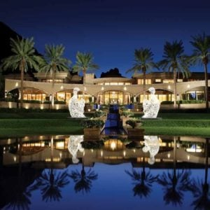 This is a look at the back of the mansion with beige exteriors complemented by the warm lights of the windows, glass walls and the line of tropical trees. You can also see here the large pool at the back of the house adorned with a couple of large sculptures. Image courtesy of Toptenrealestatedeals.com.