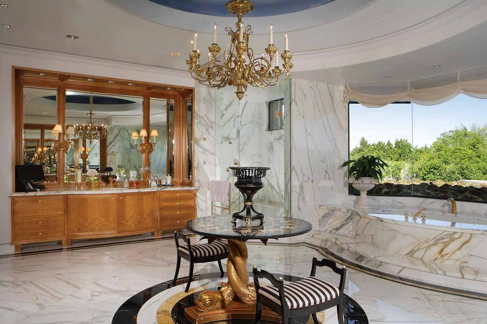 This bathroom has a white marble bathtub under the large window next to the small round table that is topped with a chandelier. Image courtesy of Toptenrealestatedeals.com.
