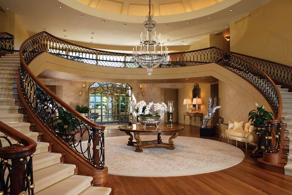 Upon entry of the mansion, you are welcomed by this grand foyer with curving stairs, a tall beige ceiling and a chandelier hanging over a wooden round table in the middle. Image courtesy of Toptenrealestatedeals.com.