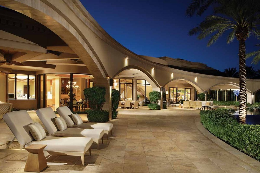 This is a look at the patio of the mansion with large beige concrete arches adorned with outdoor lights. This area is fitted with multiple lawn chairs with matching beige cushions. Image courtesy of Toptenrealestatedeals.com.