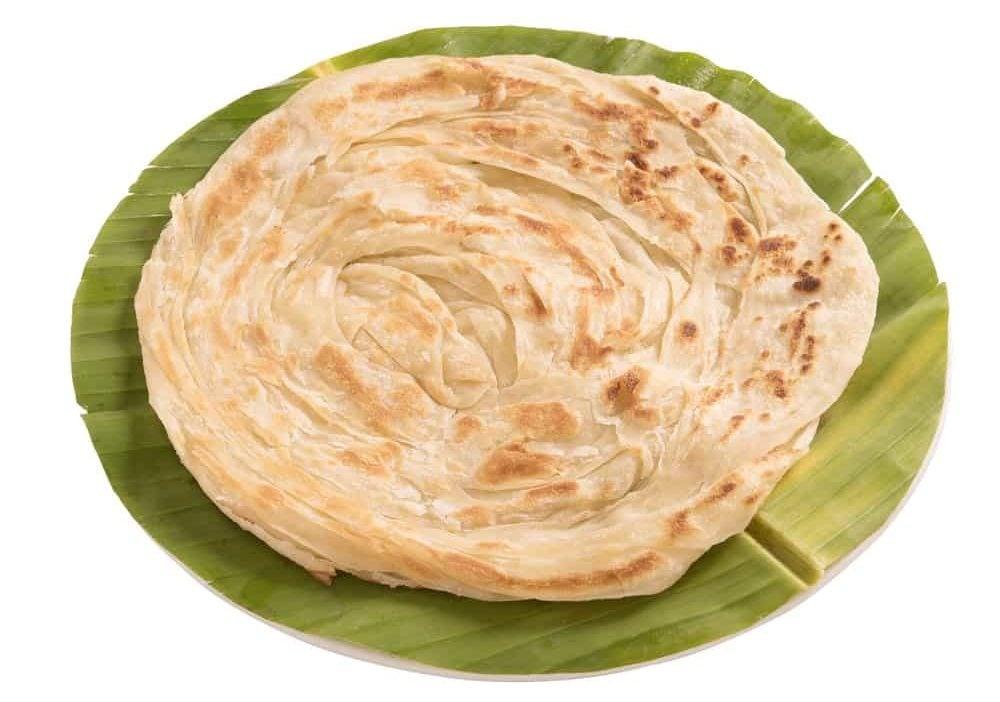 Paratha bread on a round cut banana leaf.