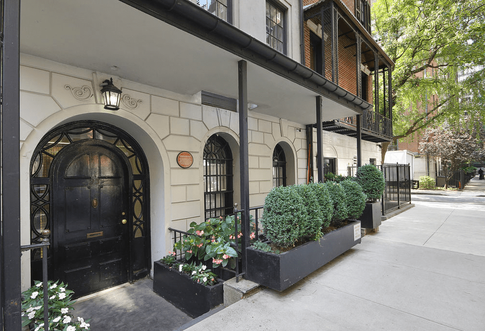 This is the street-level view of the main entrance of the townhome. This features an arched black main door that matches the arched windows on the side contrasted by white walls and complemented by planters of shrubs. Image courtesy of Toptenrealestatedeals.com.